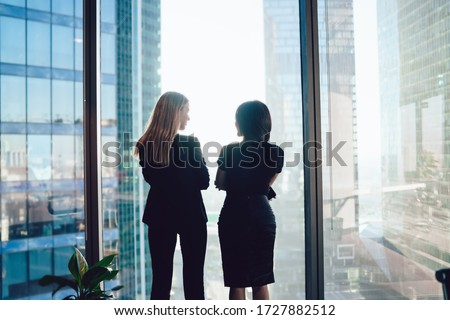 Back view of female colleagues in formal wear standing near window and communicating about cooperation in business center, confident women together planning future success of brainstorming ストックフォト ©