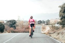 Back view of female cyclist cycling to the village. She is riding a bike on a road on the countryside. She is wearing colorful short cycling wear and white and red helmet