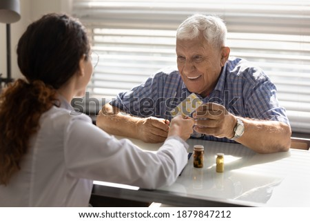 Back view of female doctor give pills medication to smiling mature male patient in private hospital. Woman GP or nurse recommend treatment, offer drugs medicines to happy elderly man client in clinic. Foto stock ©