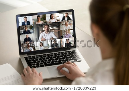 Back view of female employee engaged in web team meeting briefing using laptop at home, have webcam conference, woman worker talk on video call with diverse multiracial colleagues on computer