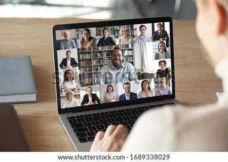 Back view of female employee speak talk on video call with diverse multiracial colleagues on online event briefing, woman worker have Webcam group conference with coworkers on modern laptop at home