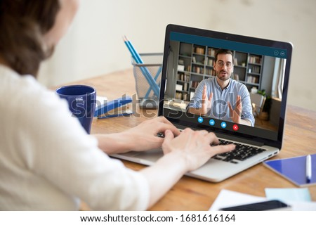 Back view of female employer talk interview confident male job applicant via online video call on laptop, businesswoman speak hire work candidate or consult client, use webcam conference on computer