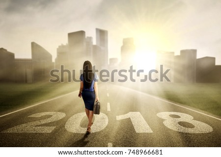 Back view of female entrepreneur carrying a briefcase while walking in the road with numbers 2018