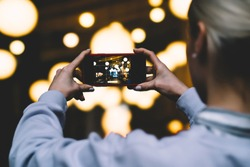 Back view of female holding with hands in horizontal position mobile phone and photographing gold shinning lights on digital high quality camera.Woman taking picture on smartphone with image on screen