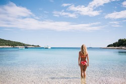 Back view of female in swimsuit standing on shallow in sea getting sunbathed looking at calm water surface and harbour, blonde woman 20s with slim figure recreating on beach in summer on vacations