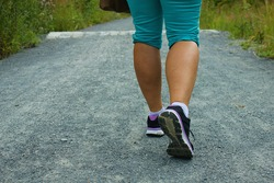 Back view of female legs with sport shoes walking on a gravel trail