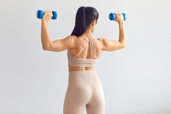 Back view of female model posing in studio and demonstrating comfortable activewear. Rear view of young woman in modern light beige close-fitting sportswear holding blue dumbbells and showing fit body