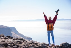 Back view of female photographer in casual clothes with backpack and photo camera celebrating achievement of top of rocky cliff with raised arms during trip in United States