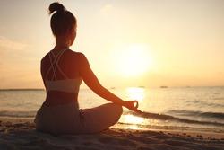 Back view of female sitting in Padmasana while meditating alone on seashore against sky in sundown light