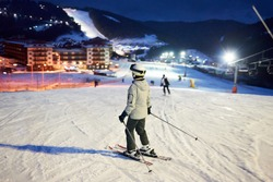 Back view of female skier after skiing day standing on skis, looking on wonderful ski resort lighted by lanterns and enjoying with fascinating views in darkness. Mountains views on blurred background.