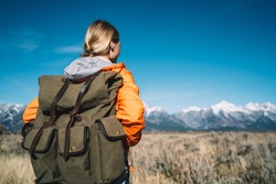 Back view of female tourist in orange jacket and hiking backpack strolling in national park enjoying free time vacations getaway, caucasian woman traveler exploring nature environment on weekend