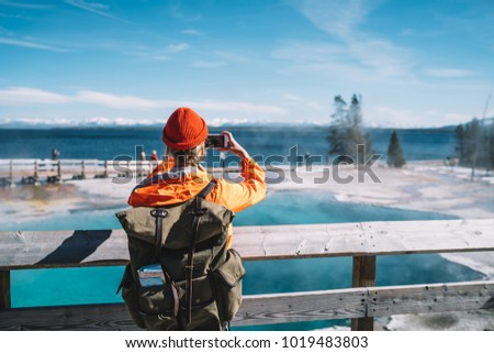 Back view of female tourist with backpack using smartphone for taking picture of hot springs, hipster wanderlust making image on smartphone camera of touristic place in USA with geyser in Yellowstone #1019483803