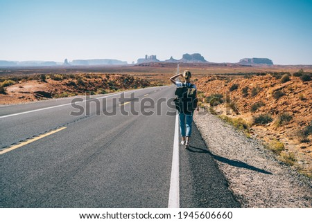 Back view of female traveler in casual wear with backpack going along asphalt road towards Monument Valley with one arm raised