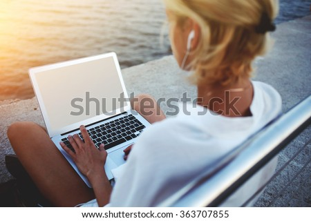Back view of female using net-book with blank copy space screen for your text message or promotional content, young woman reading news via laptop computer while sitting near sea during her vacations