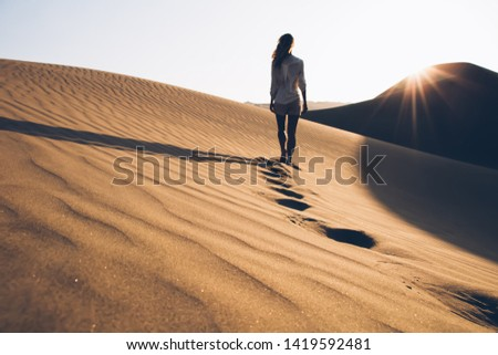 Back view of female wanderer in casual wear exploring wild Sahara desert during summer evening in nature environment, woman tourist walking in sands wilderness discovering hot Egypt climate #1419592481