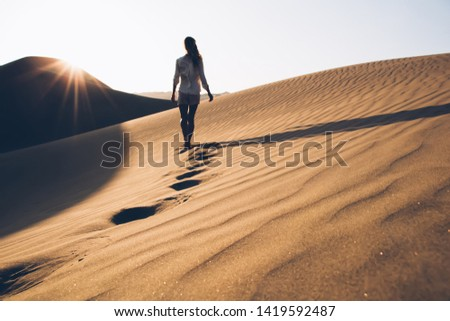 Back view of female wanderer in casual wear exploring wild Sahara desert during summer evening in nature environment, woman tourist walking in sands wilderness discovering breathtaking Safari #1419592487