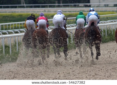 Back view of five horses and jockeys racing on sandy track, Hippodrome, Pyatigorsk, Russian Federation.