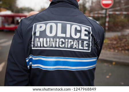back view of french policeman police municipal means local police in french #1247968849