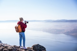 Back view of full body of female photographer with backpack and photo camera taking picture of amazing scenery with foggy landscape and river in sunny day