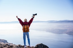 Back view of full length of female photographer with photo camera  enjoying picturesque landscape while standing on rocky cliff with raised arms and celebrating victory of successful achievement