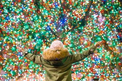 Back view of girl on the background of the Rockefeller Christmas tree in New York. Beautiful Christmas Tree at Rockefeller center at Xmas eve and lights