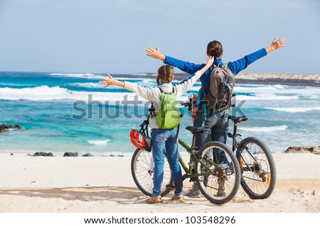Back view of girl with her mother having a weekend excursion on their bikes on a summer day in beautiful sea landscape