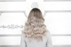 Back view of girl with pretty blond ombre hairstyle standing in hair salon, Balayage technique concept