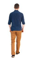 Back view of going  handsome man in jeans and a shirt.  walking young guy .  Isolated over white background.  man in brown pants, shirt sleeves rolled away into the distance.