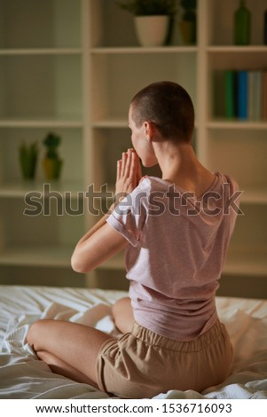 Back view of gorgeous young caucasian female with short hair in prayer position, keep eyes closed, meditating at home alone, keeping calm