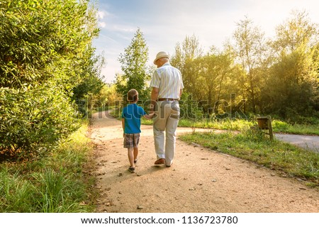 Back view of grandfather with hat and grandchild walking on a nature path Stock photo ©