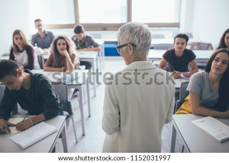 Back view of grey-haired woman teacher stading at classroom and talking to high school students.