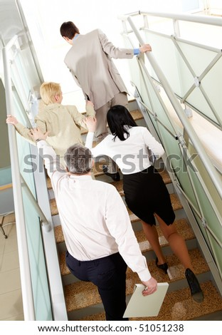Back view of group of business people going upstairs in office building