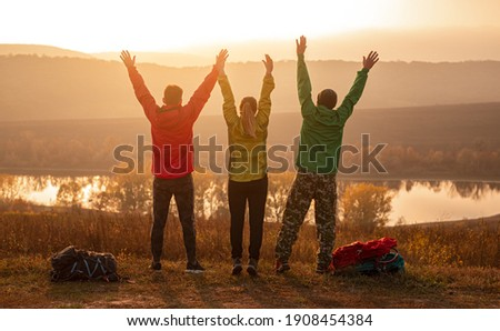 Back view of group of unrecognizable friends in activewear with backpacks raising arms and enjoying freedom while standing near lake, and resting after trekking at sunset time in autumn countryside