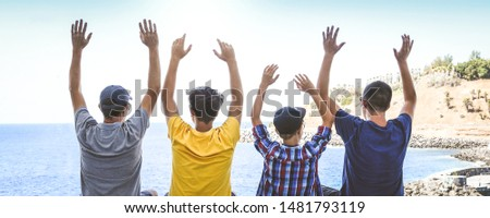 Back view of group of young people raising hands. Panorama image of father and sons enjoying tropical summer holidays. Blue sky and sea in background. Freedom, vacation, travel, happiness concept