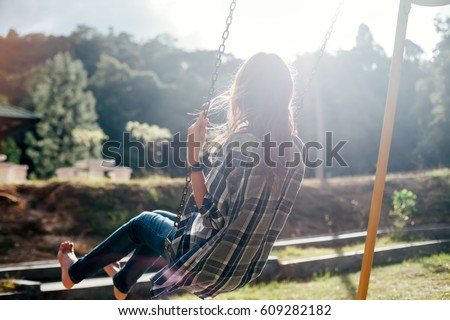 Back view of happy barefoot girl on swing in sun light. Carefree woman #609282182