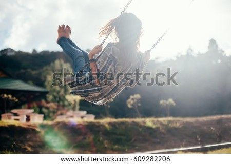 Back view of happy barefoot girl on swing in sun light. Carefree woman