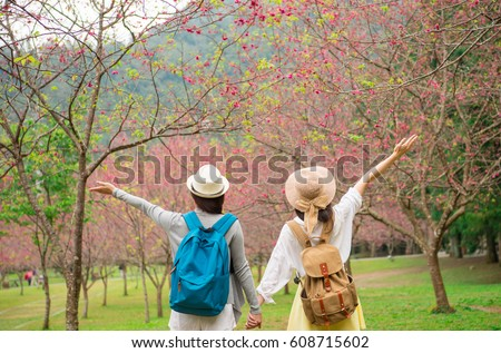 Back view of happy winner friends cheering with arms up of blooming cherry blossom at sakura avenue of japan having fun during spring travel. Young asian girl tourists at beauty flower garden in korea #608715602