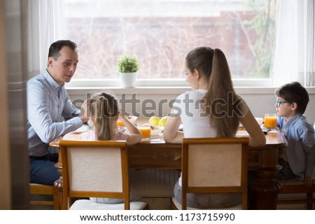 Back view of happy young family of four having breakfast together at home, millennial parents enjoy spending time with kids eating healthy tasty food in kitchen, mom dad and children talk at table