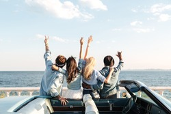 Back view of happy young friends standing with raised hands near the car
