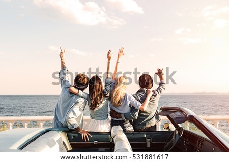 Back view of happy young friends standing with raised hands near the car #531881617