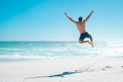 Back view of happy young man jumping with outstretched arms on the beach with copy space. Rear view of shirtless guy wearing swimwear and having fun at beach. Carefree and freedom concept on vacation.