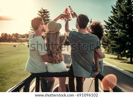 Back view of happy young people clinking bottles of beverage and talking while travelling by car in sunny weather