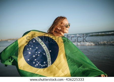 Back view of happy young woman in sunglasses and Brazilian flag in sunlight against of seaside