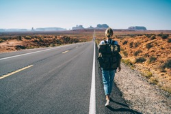 Back view of hipster girl wanderlust walking on asphalt road in wild lands on southwest getting to National park by foot, female tourist with rucksack having journey in Arizona hitchhiking on the way