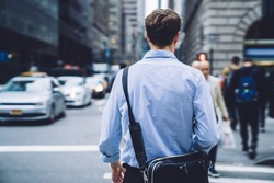 Back view of intelligent male economist with trendy leather briefcase walking to business meeting in financial district, clever professional proud ceo in blue t shirt going to destination in downtown