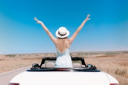 Back view of joyful young female in summer clothes in cabriolet during road trip