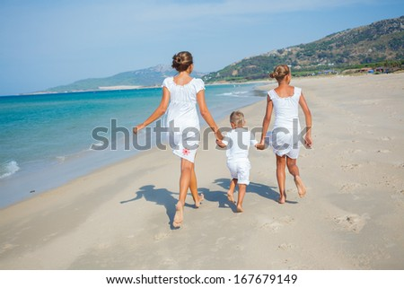 Back view of kids running on beach vacation