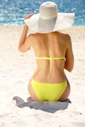 Back view of lady with bonnet sitting on the beach