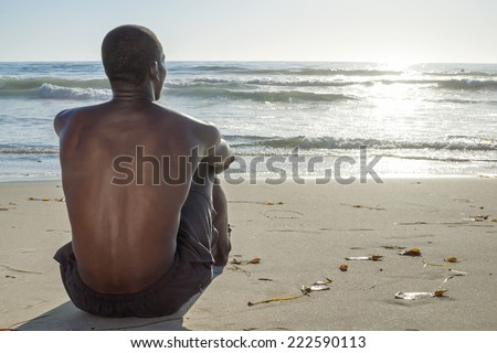 Back view of lean young shirtless African American man sitting on sand while watching waves roll in on beautiful beach under setting sun #222590113