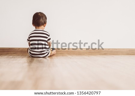 Back view of Little baby boy sitting alone and watching smartphone.Vintage tone.